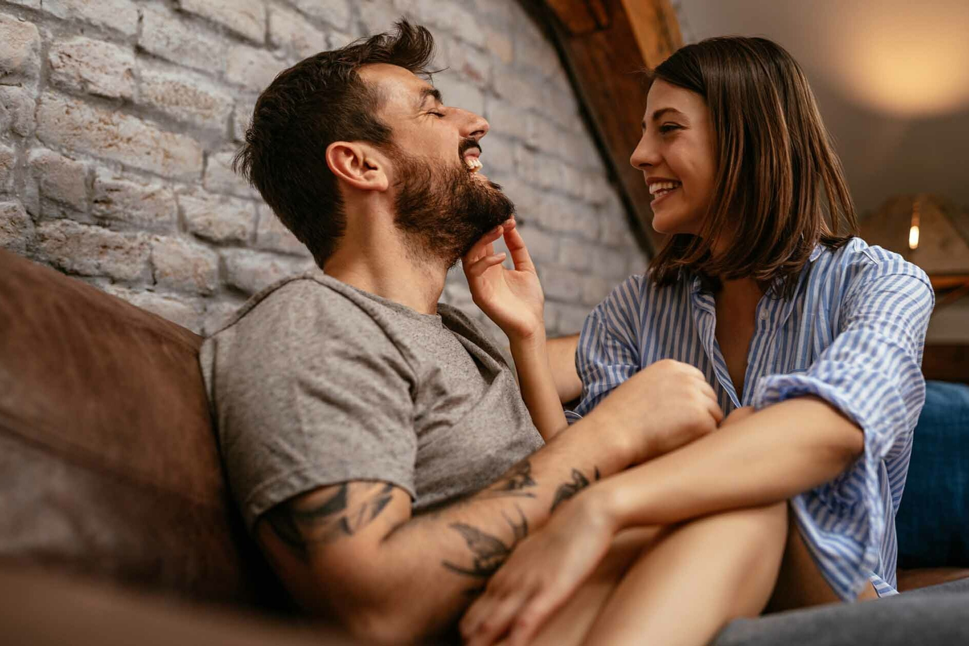 Playful Couple Cuddles on Couch Laughing at Bad Dating Advice