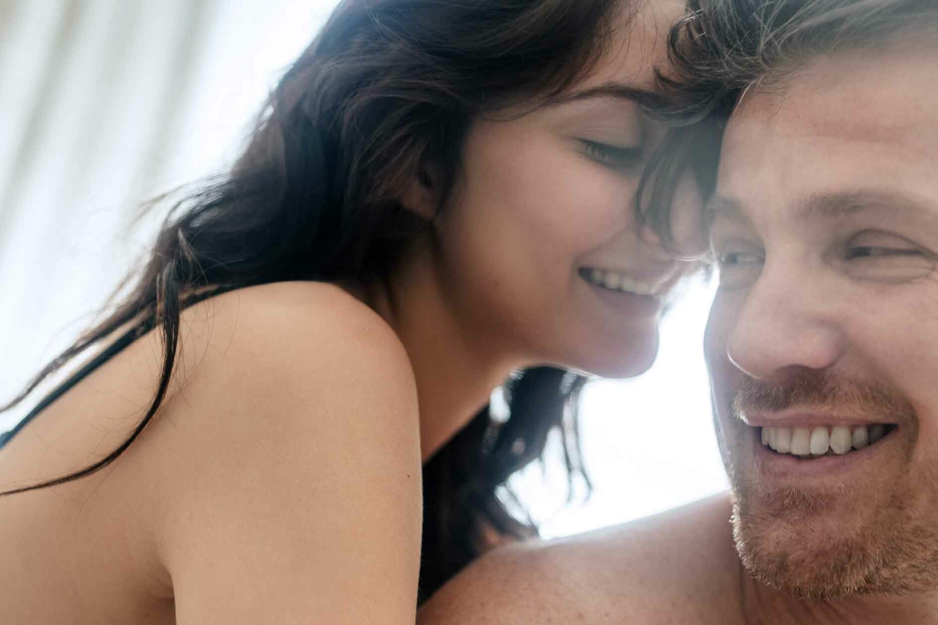 Couple in Bed Together Sharing Intimacy and Laughing