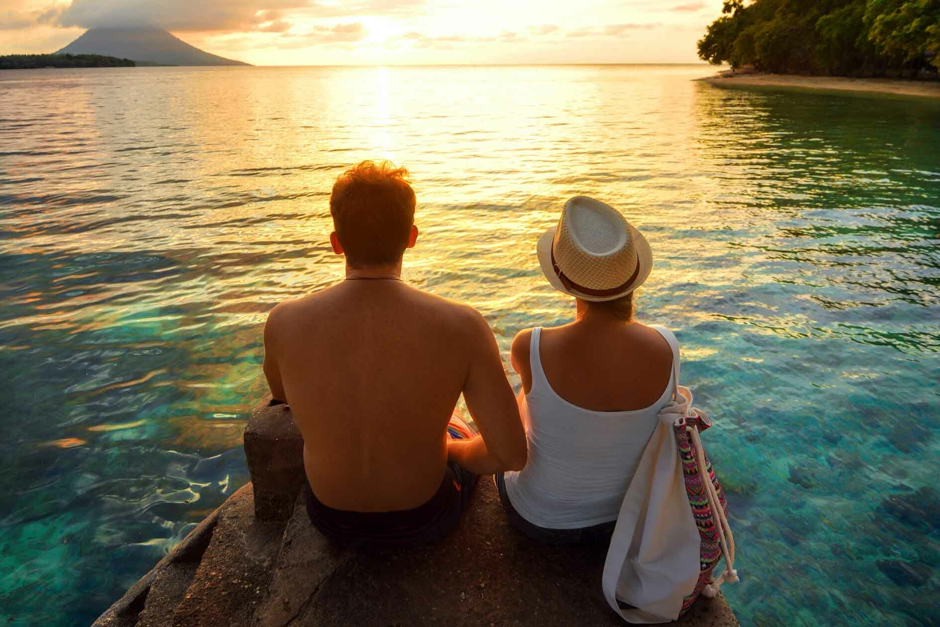 Couple sitting on a rock overlooking a beautiful beach