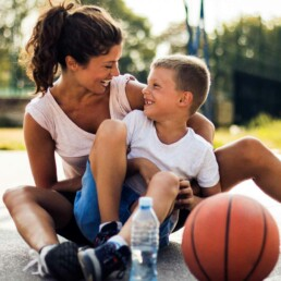 Single Mom and son laughing while on basketball court